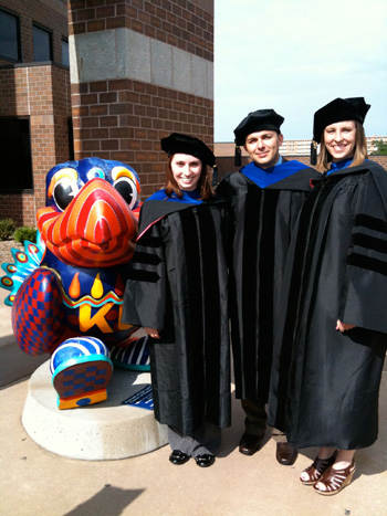 A picture of Linda Blake in her graduation gown with fellow graduates next to a Jayhawk statue.
